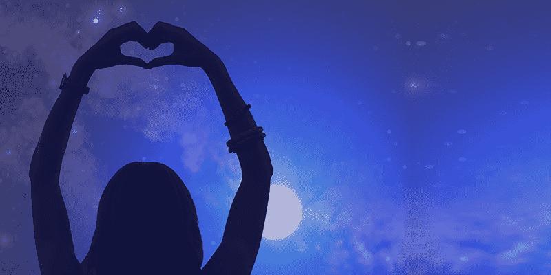 Mulher olhando para o céu e a Lua com os braços levantados formando um coração com as mãos