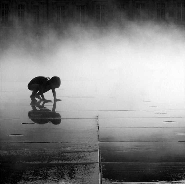 Menino coloca as mãos no chão e agachado faz um belo reflexo. O mundo exterior reflete o ser interno.