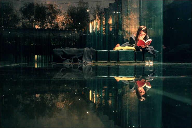 Mulher concentrada em sua leitura não observa seu belo reflexo. O mundo exterior reflete o ser interior.
